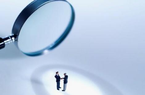 Magnifying glass focused on two professional men